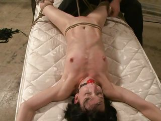 Brunette bitch Elise is tied on a mattress and she's afraid of what will happen. The slut has been ball gagged and the executor comes at her, uses rope to tie her hard and even torment her cunt with it. He then rubs her pussy with that vibrator, lifts this cunt up and hangs her in a very uncomfortable position.
