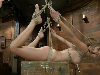 Hanging blonde with suckers on her hard nipples is taking the dildo her mistress handles deep and harsh. Her pink shaved vagina barely takes it and she moans with her mouth that has been gagged with a ball. Look at her hanging there, enjoying her punishment, wanna see some more?