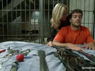 Looks like this hottie blonde milf, Simone Sonay is some kind of in-charge in a prison facility. Now here she is horny and crazy, submitting herself to a random prisoner named Ramon Nomar. He's playing with her with the toys she brought and in no time he starts fucking her like a bitch from behind!