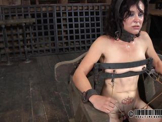 That chair is perfect for miss James. She's naked, strapped on it and a bit terrified with what's about to happen. The executor gapes her cunt using metal clamps and some kind of dildo is filling her womb. The lovely brunette endures her punishment and step by step she learns to like it!