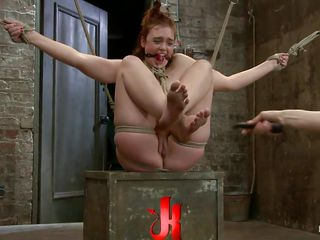 Horny redhead Jodi enjoys being all tied up and getting her pussy whipped by a female executor. She moans with pleasure, while her dirty mouth is gagged. The slut is lifted in the air and is held like this only with ropes. She is grateful for being fingered and having a big vibrator on her wet shaved cunt!