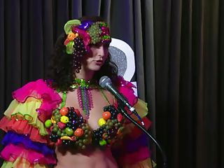 The hosts of Playboy Radio's Morning Show are looking at their guest model who is wearing the costume she'll be wearing to the Playboy Mansion for Halloween. Her head and tits are covered in fake fruit like oranges, limes, lemons, and more. She flashes her breasts for the hosts and viewers.