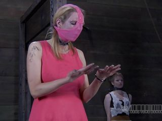 Pink is the color she loves, hope her pussy is just as pink as her mask. The sweet chick Alani is in the middle of the vault with her arms tied and her legs secured in a bondage device. She awaits her punishment so nicely dressed and another doll is in the back of the room, quietly enjoying herself.