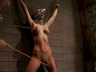 Watch this slut as she is tied on the wall and has a bag on her head. She is suffocating slowly and to increase the pleasure of being dominated they punish her hot body by spanking her on the thighs and belly with a stick. After spanking she receives a vibrator on her cunt and moans with pleasure and pain. She's so hot with those clamps on her hard nipples and, will they add more weights?